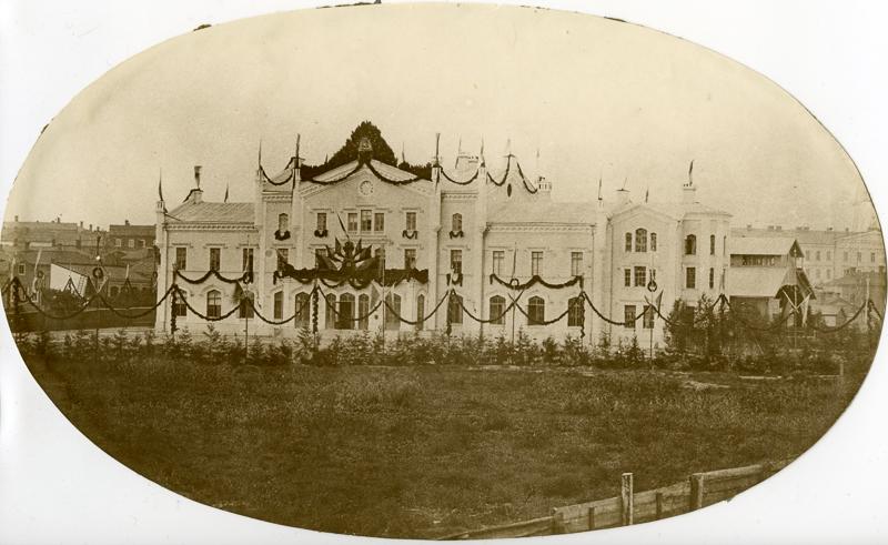 Asemarakennus koristeltu köynnöksillä. Rakennuksen edessä havupuita ja nurmikenttä.
