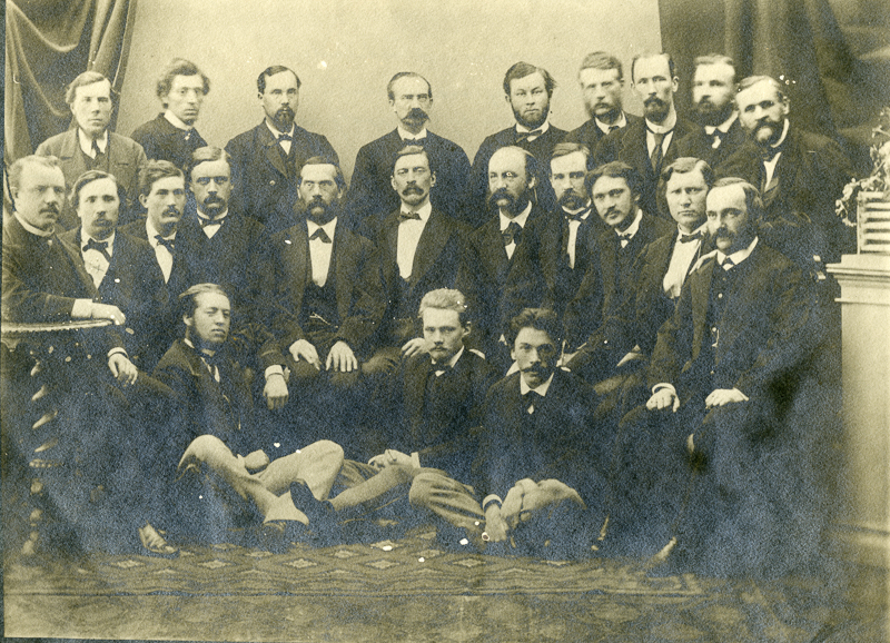 Tummiin pukuihin pukeutuneita miehiä ryhmäkuvassa.