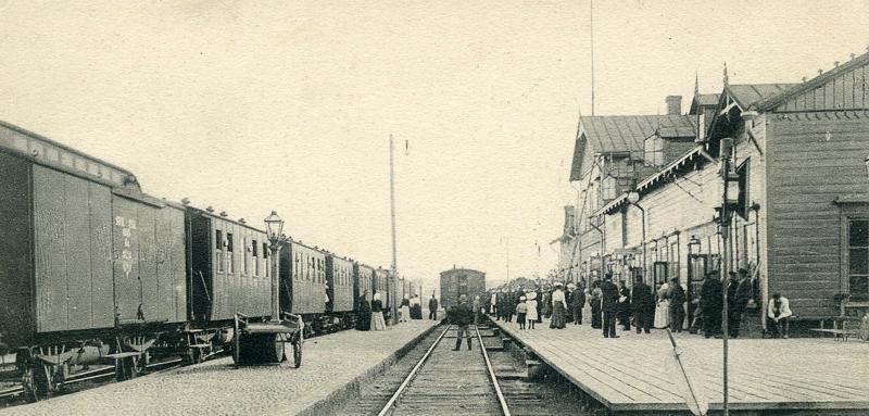 Asemarakennuksen edustalla on asemalaituri, jolla seisoo paljon ihmisiä. Kaksi raidetta, joilla molemmilla on vaunuja. Myös raiteiden välissä on laituri, jolla seisoo ihmisiä.