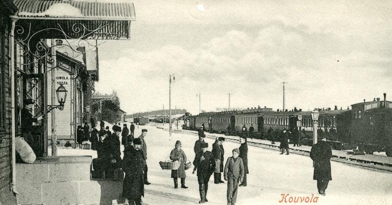 Asemalaiturilla aseman edessä seisoo ihmisiä. Raiteella on juna.