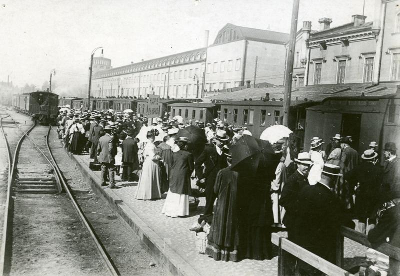 Suuri joukko ihmisiä nousemassa laiturilla seisovaan junaan. Taustalla on aseman rakennuksia.