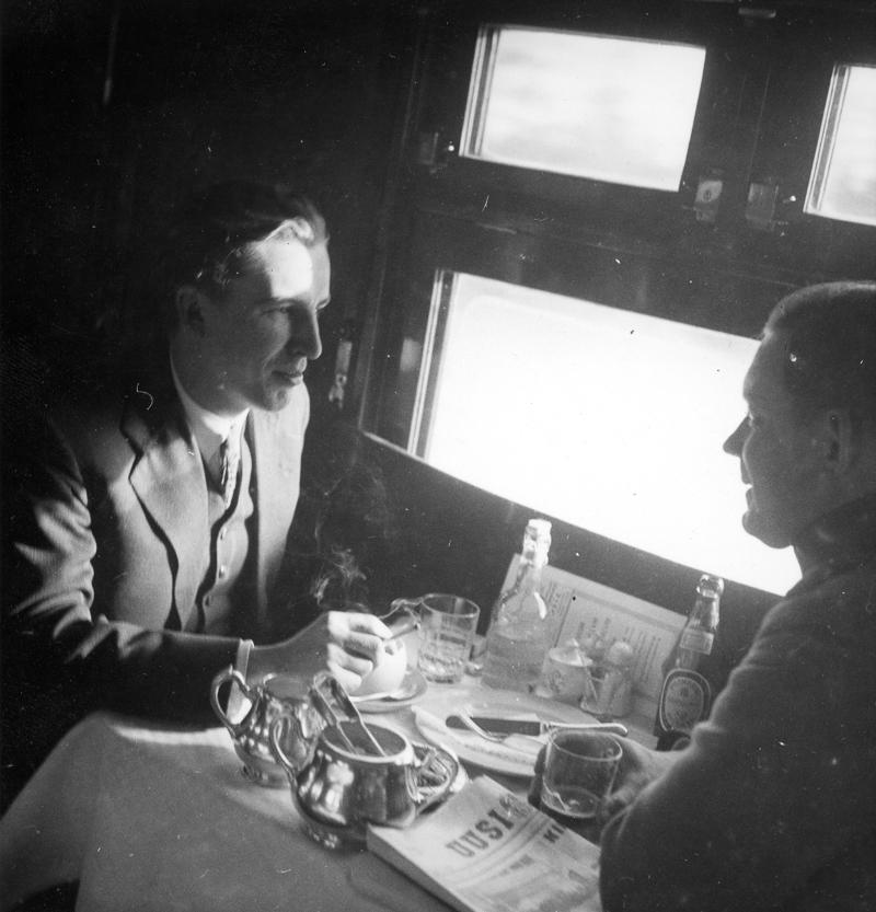 Kaksi matkustajaa istumassa katetun pöydän ääressä ikkunan luona.