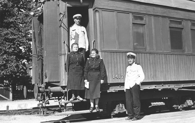 Raiteilla seisova vaunu, jonka portailla ja edustalla seisoo junan henkilökuntaa.