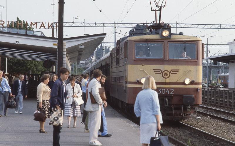 Lähiliikenteen juna raiteella asemalaiturin luona. Katetulla laiturilla seisoo matkustajia. Taustalla raiteita, ratapihaa ja metsää.