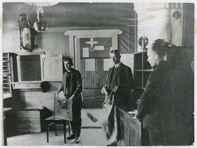 Kolme miestä seisoo huoneessa, yhdellä on käsissään postisäkki ja toisella sanomalehti ja laukku. Huoneessa on hyllyjä ja kaappeja, seinällä on koristeellinen kello ja taustalla oviaukko toiseen huoneeseen.