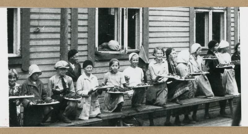 Asemalaiturilla istuvia lapsia ja aikuisia, joilla on sylissään marjatarjottimia.