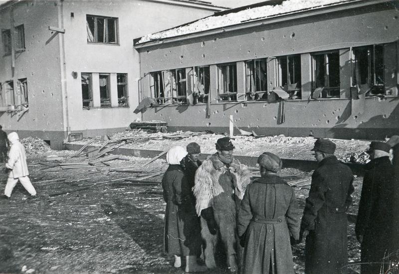 Vaurioitunut rakennus, jonka edessä on kiviä ja romua. Edustalla seisoo sotilaita ja virkapukuisia miehiä.