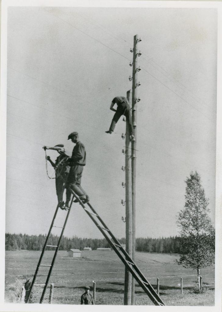Kaksi miestä työskentelee vastakkain asetetuilla tikapuilla ja kolmas mies työskentelee ylhäällä lennätinpylväässä. Yksi mies seisoo pylvään juuressa. Taustalla on aita, puu, peltoa, rakennuksia ja metsää.