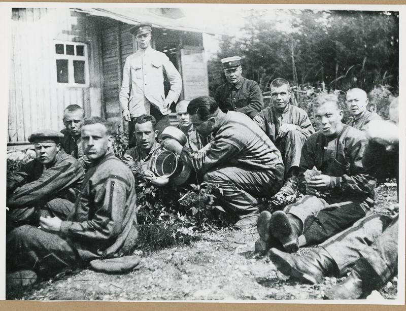 Vankeja ja vartijoita ryhmäkuvassa. Taustalla puinen rakennus ja metsää.