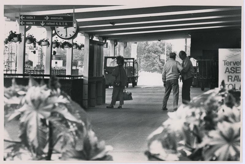Asemalaiturin katoksen alla on kolme ihmistä. Kuvan edustassa on kukka-asetelmia, ja vasemmalla näkyy opastekylttejä raiteille ja asemalle sekä laiturin kello. Taustalla  on puita ja ratapihan rakennuksia.