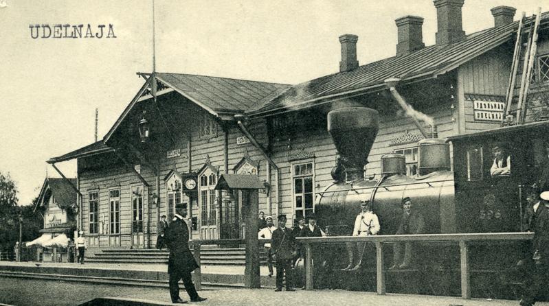 Asemarakennuksen edessä seisoo vanha höyryveturi. Veturin luona ja ympärillä seisoo ihmisiä.