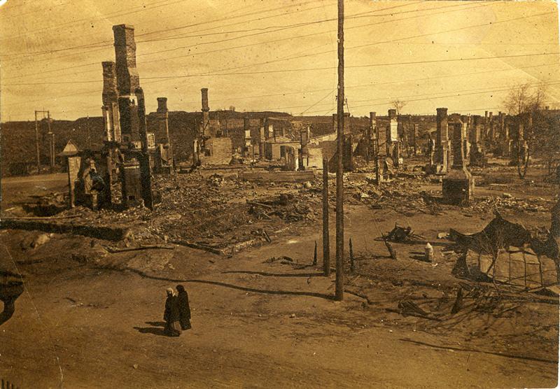 Tuhoutuneita rakennuksia, joista jäljjellä perustuksia ja savupiippuja. Edustalla kävelee kaksi naista.