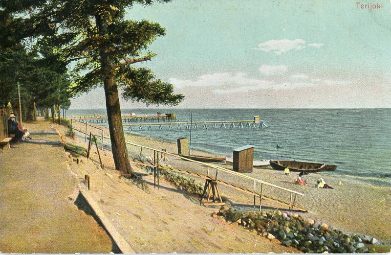 Hiekkaranta, jota vasemmalla reunustaa kävelytie. Kävelytien varrella on penkki, jossa istuu ihmisiä. Rantaan johtaa kävelytieltä portaat ja rantaviivalla on veneitä. Rannallla on ihmisiä ja kaksi laituria.