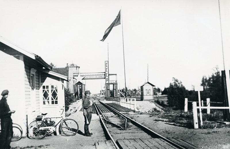 Raide ja rautatiesilta Suomen ja Neuvostoliiton rajalla. Raiteen yllä näkyy suuri tähti ja teksti CCCP. Lipputangossa liehuu lippu ja raiteen vieressä seisoo sotilas. Vasemmalla seisoo toinen ihminen.