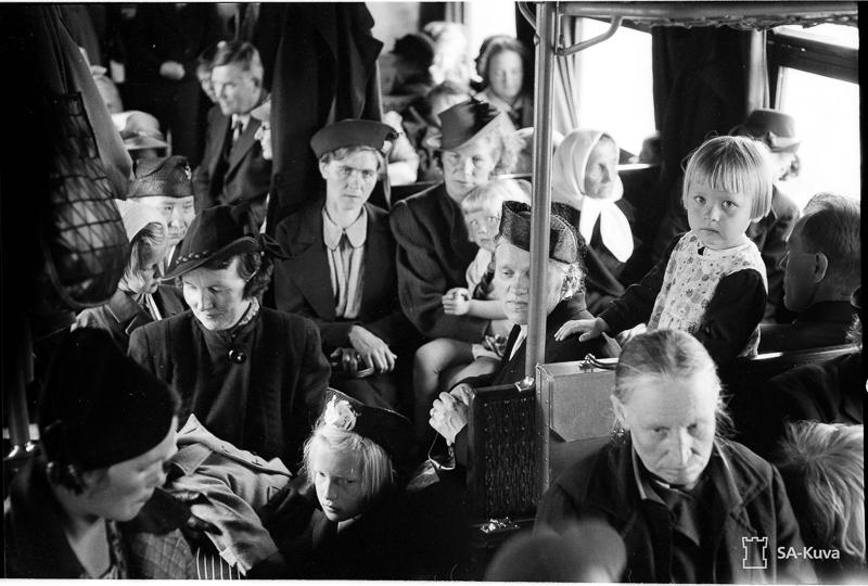 Junavaunussa istuu matkustajia.