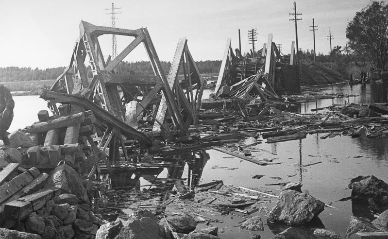 Tuhoutunut silta, jota ympäröi vesi. Vedessä on paljon romua ja suuria kiviä. Taustalla on metsää.