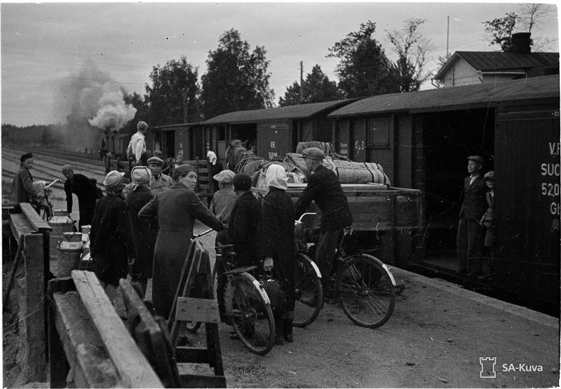 Asemalaiturilla on ihmisiä jalkaisin ja polkupyöärillä. Laiturilla on myös hevosen vetämät kärryt, joissa kuorma. Raiteella seisoo veturi, jonka perässä on avoimia tavaravaunuja. Vaunun ovella seisoo kaksi poikaa.