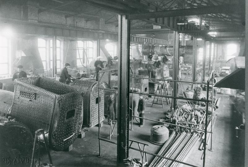Höyryveturien kattiloita, työkaluja ja rakennustarvikkeita. Miehiä työskentelemässä.