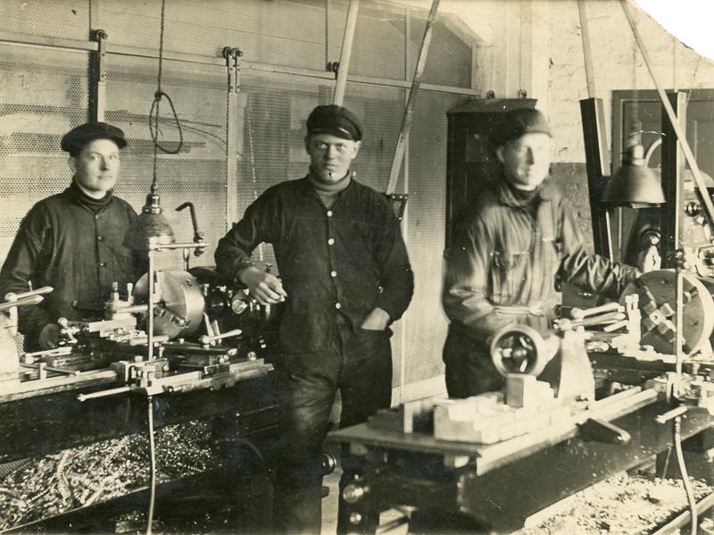 Kolme nuorta miestä seisoo sorvipöytien äärellä työskentelemässä.