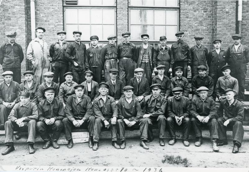 Miehiä työhaalareissa ryhmäkuvassa.