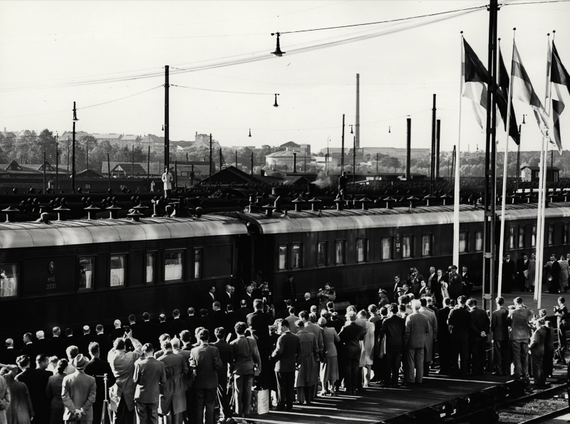 Juna raiteella, laiturilla paljon ihmisiä vastaanottamassa junasta nousevia vieraita. Suomenliput liehuvat lipputangoissa.