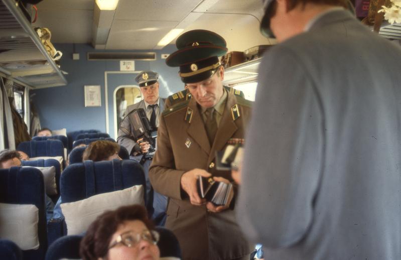 Virkapukuiset miehet keräävät matkustajilta passeja junassa.