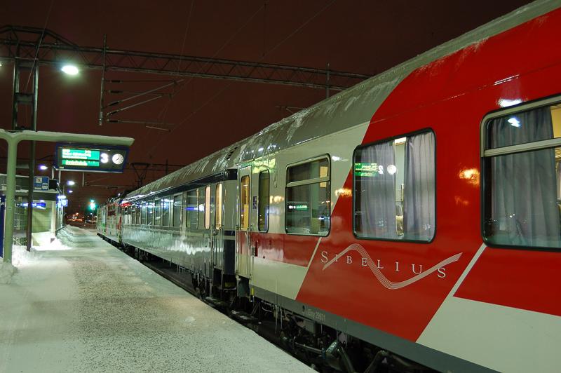 Punasävyinen juna laiturilla iltahämärässä.