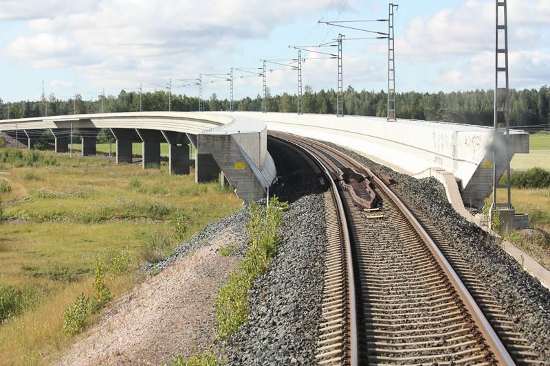 Vasemmalle kaartuva rautatiesilta, jota reunustaa molemmin puolin valkoinen betoniaita. Sillan alla on niittymäistä maastoa ja taustalla näkyy metsää ja peltoa.
