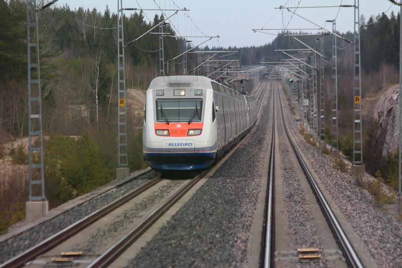 Allegro-juna kulkee raiteilla. Raiteiden molemmilla puolilla on kallioita ja metsää, ja raiteita reunustaa sähkölankoja kannattelevan tolpat. Taustalla on radan molemmilla puolilla valo-opasteet, oikealla puolella valo on vihreä ja vasemmalla punainen.
