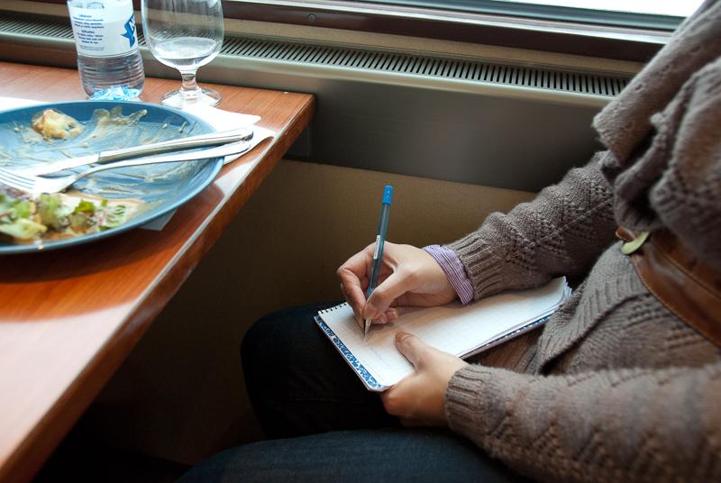 Pöydän ääressä istuvan henkilön sylissä on kirjoituslehtiö ja hän kirjoittaa lehtiöön kuulakärkikynällä. Pöydällä on lautanen, aterimet, lasi ja vesipullo.