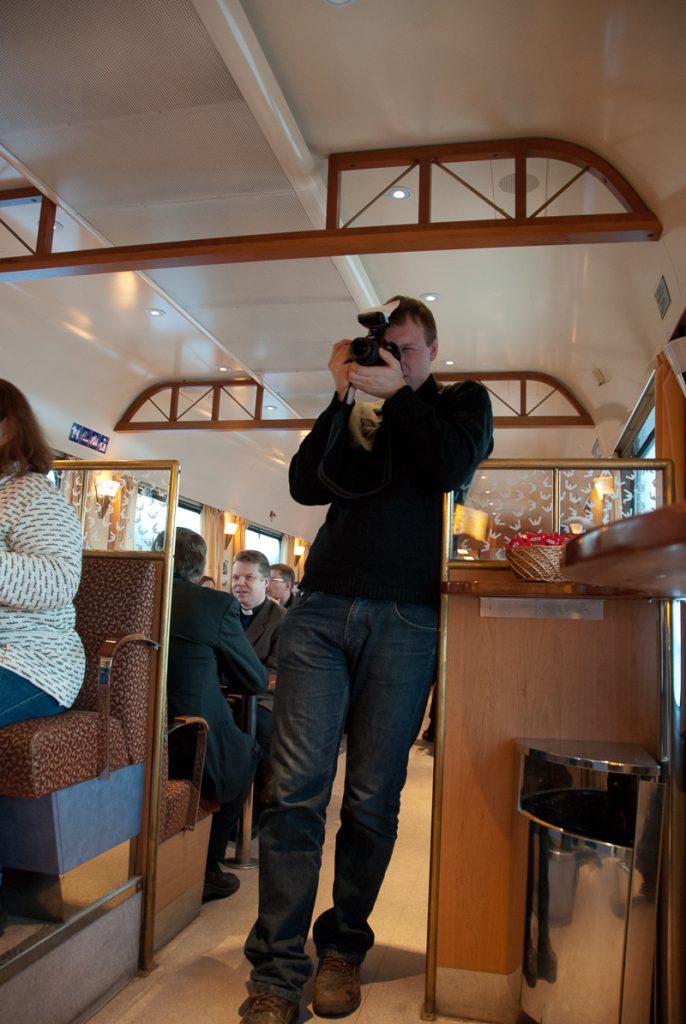 Mies ottaa valokuvaa ravintolavaunun käytävällä. Taustalla on ravintolavaunun asiakkaita pöytien ääressä.