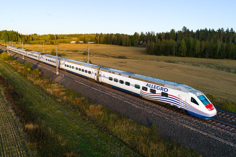 Allegro-juna kulkee raiteilla, ympärillä peltoa ja metsää.