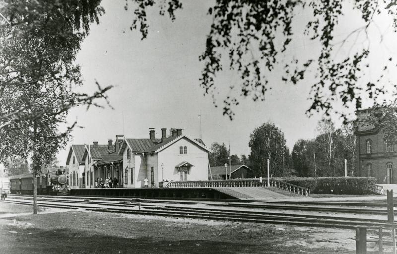 Asemarakennus, jonka edessä seisoo vanha juna. Asemalaiturilla on ihmisiä. Laiturin edessä on junaraiteita. Asemarakennuksen takana näkyy matala rakennus, jonka takana ja vieressä on puita. Oikealla on tiilirakennus.