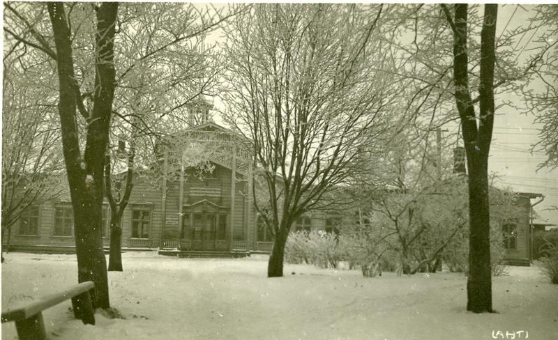 Asemarakennus näkyy puiden ja pensaiden takana. Maassa, oksilla ja rakennuksen katolla on lunta.