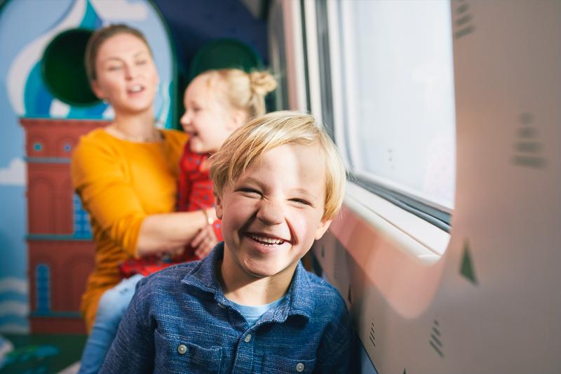 Hymyilevä lapsi junan ikkunan vierssä. Taustalla on nainen ja toinen lapsi, ja heidän takanaan on värikäs kuva kupolikattoisesta tornista.