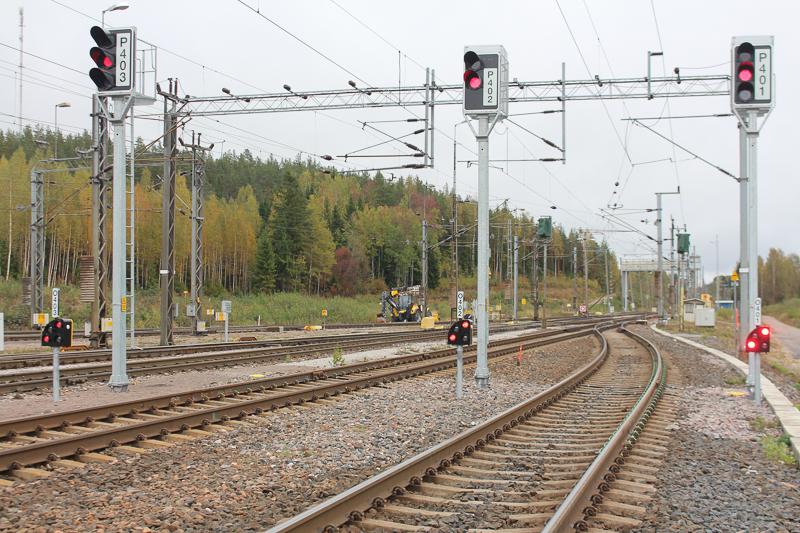 Vierekkäisiä raiteita ja valo-opastimia, joissa on punaiset valot. Raiteiden yllä kulkee sähkölankoja. Taustalla näkyy traktori ja metsää.