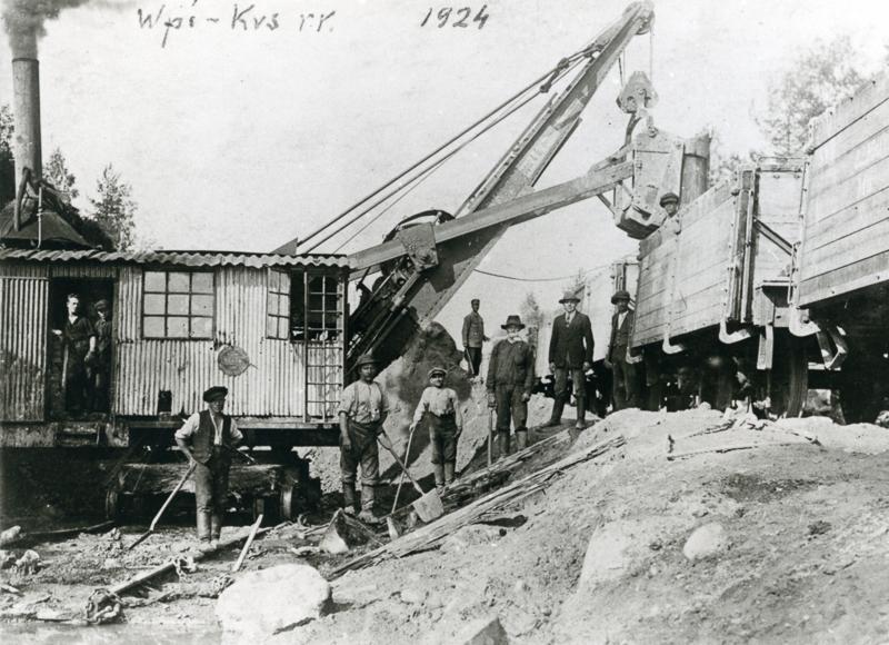 Höyrykaivinkone lastaa hiekkaa junanvaunuun. Ympärillä radanrakentajia.