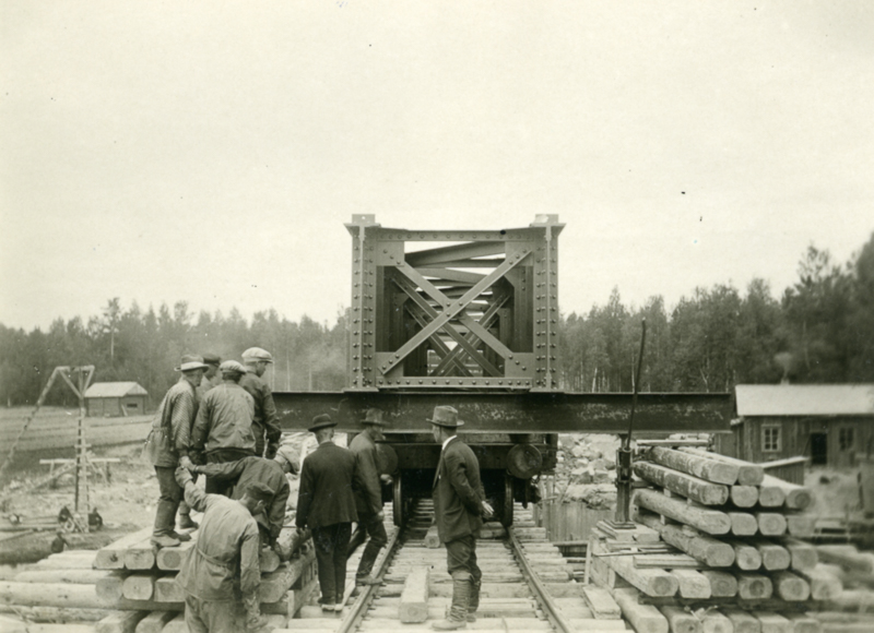 Siltapalkkia kuljetetaan radanrakennustyömaalla tavaravaunussa.