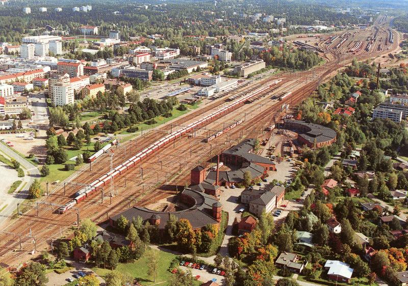 Ilmakuva, jossa näkyy keskellä useita raiteita, joilla seisoo junia. Radan ympäristössä on rata-alueen rakennuksia, parkkialueita, ja kaupungin taloja. Alueella on nurmialueita ja puita, ja taustalla on metsää.