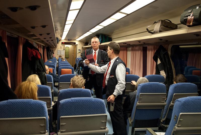 Kaksi konduktööriä junan käytävällä tarkastaa passeja. Käytävän molemmilla puolella istuu matkustajia.