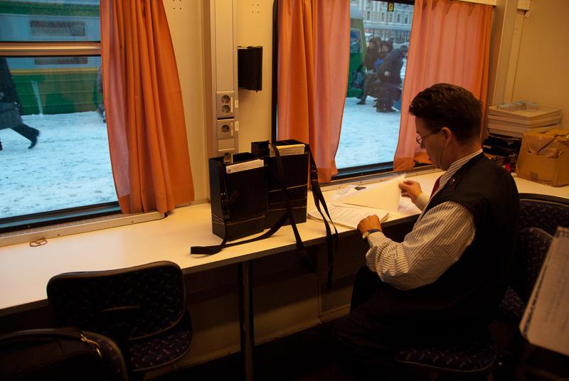 Konduktööri istuu junan ikkunan luona tarkastelemassa papereita. Ikkunoista näkyy kaupunkia ja ihmisiä matkatavaroiden kanssa.