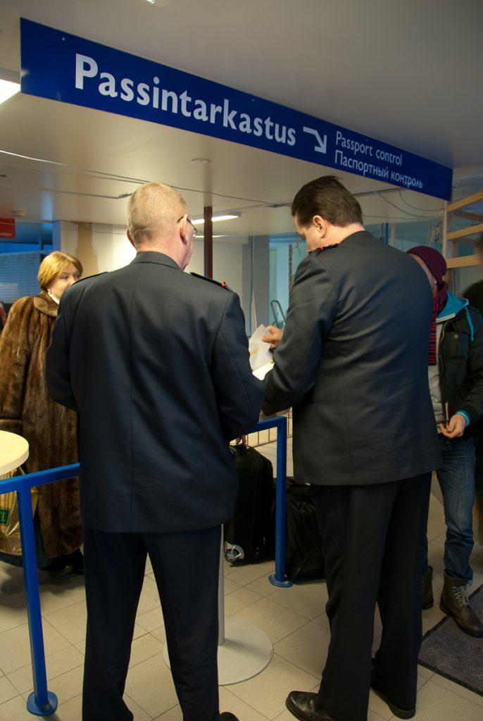Kaksi konduktööriä selin kameraan passintarkastusopasteen luona. Taustalla on matkustajia.