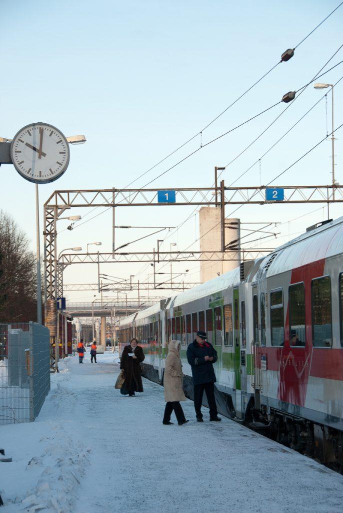 Raiteella seisova juna, johon konduktööri opastaa matkustajia. Hiekoitetulla asemalaiturilla on lunta. Taustalla näkyy kaksi henkilöä työvaatteissa, radan ylitse kulkeva silta ja rakennuksia.