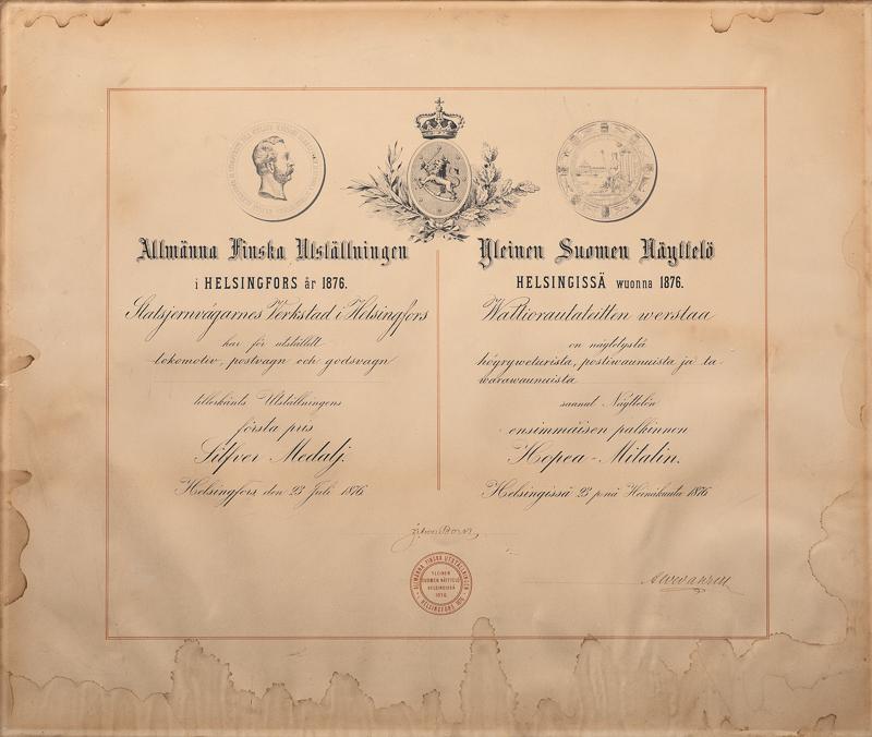 Vanha paperiarkki, jossa veturille myönnetty kunniakirja vuodelta 1876. Yläosassa vaakuna sekä kaksi muuta merkkiä. Niiden alle kirjoitettu veturin näyttelyssä saama ensimmäinen sija ruotsiksi ja suomeksi, ja kaksi allekirjoitusta.