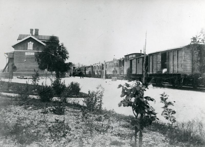 Juna seisoo raiteella aseman edustalla. Lumisella laiturilla on matkustajia.