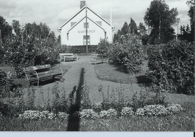 Rakennuksen edustalla oleva puisto, jossa on neljä penkkiä puistokäytävän varrella. Puiston nurmikentillä kasvaa kukkia ja pensaita. Taustalla on puita.