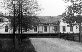 Asemarakennus, jonka edustalla on raiteita sekä nurmikentän ja puiden reunustama tie.
