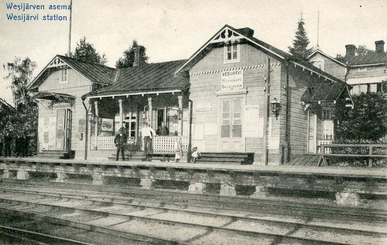 Asemarakennus, jonka kuistilla ja edessä olevalla asemalaiturilla seisoo ihmisiä. Laiturin edessä on raiteita ja aseman takana on puita ja toinen rakennus.