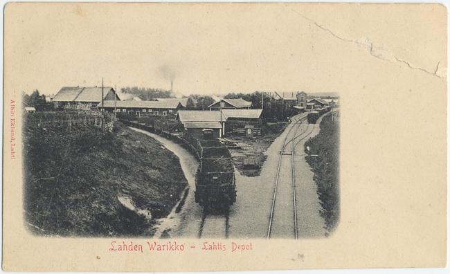Kaksi raidetta, joista toinen menee suoraan ja haarautuu ja toinen kääntyy vasemmalle. Vasemman puoleisella raiteella kulkee juna. Raiteiden välissä on rakennuksia.