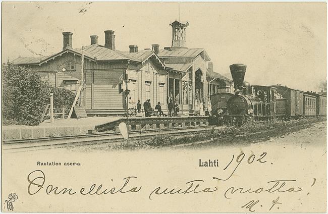 Postikortti, jonka kuvassa on asemarakennus ja asemalaiturin edessä raiteilla seisova juna. Laiturilla on ihmisiä. Kortissa on teksti Rautatien asema, Lahti, käsinkirjoitettu uuden vuoden toivotus ja vuosiluku 1902.